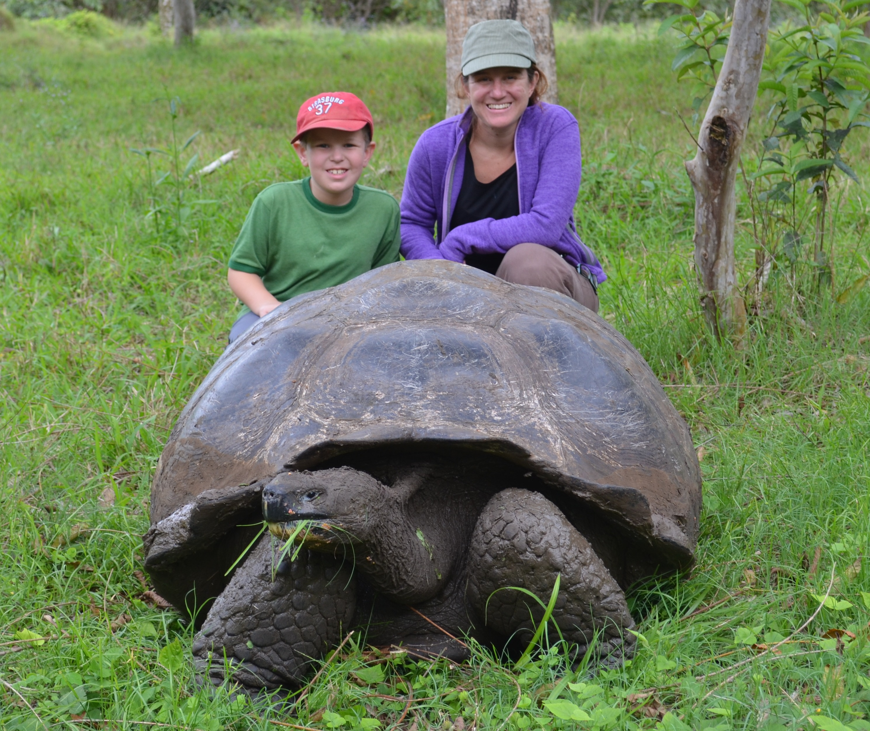 My mom and I behind a giant tortoise